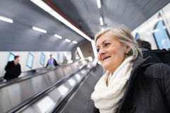 Senior woman standing at the escalator in Vienna subway. Beautiful senior woman in black coat and white woolen scarf standing at the escalator in Vienna subway Stock Images