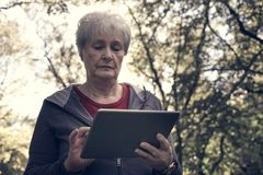 Senior woman standing in forest and typing on iPod. Clo. Serious  senior woman standing in forest and typing on iPod. Close up Stock Images