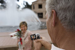 Senior woman standing beside fountain, holding bouquet of red roses, smiling, focus on man filming her with portable video recorde Royalty Free Stock Photos