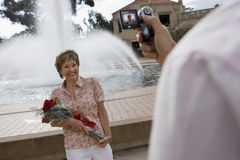 Senior woman standing beside fountain, holding bouquet of red roses, smiling, man filming her with portable video recorder (tilt,  Royalty Free Stock Image