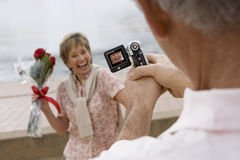 Senior woman standing beside fountain, holding bouquet of red roses, smiling, man filming her with portable video recorder (tilt,  Royalty Free Stock Photography