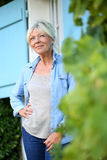 Senior woman standing in front of house Stock Photo