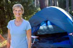 Senior woman standing in front of a tent Stock Photo
