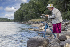 A senior woman standing with her walker by the lake and fishing. Horizontal image of an elderly senior woman with a walker fishing at the edge of the lake with Royalty Free Stock Photo