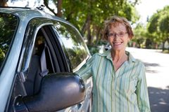 Senior woman standing near car Stock Photo