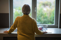 Senior woman standing near the kitchen sink and looking through window. Rear view of senior woman standing near the kitchen sink and looking through window stock image