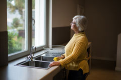 Senior woman standing near the kitchen sink and looking through window. Thoughtful Senior woman standing near the kitchen sink and looking through window stock photography
