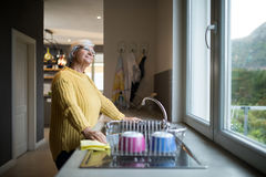 Senior woman standing near the kitchen sink and looking through window. Thoughtful Senior woman standing near the kitchen sink and looking through window royalty free stock photo