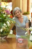 Senior woman standing near the table Royalty Free Stock Image