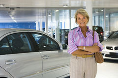 Senior woman standing beside new silver saloon car in large car showroom, smiling, portrait Stock Photo