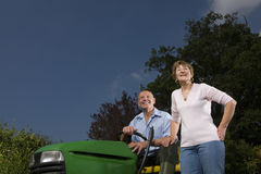 Senior woman standing next to man on riding lawn mower Stock Photography