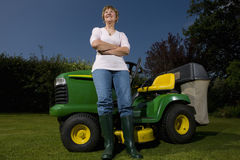 Senior woman standing next to riding lawn mower Stock Photo