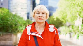 Senior woman standing outdoors. Downtown business dictrict with skyscrapers and trees on background. Blond senior woman in red coat standing outdoors. Downtown stock video footage