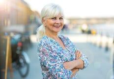 Senior woman standing outdoors Stock Photo