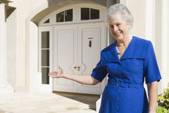 Senior woman standing outside home Royalty Free Stock Images