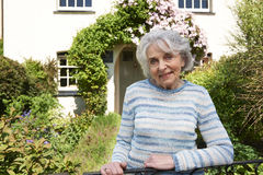 Senior Woman Standing Outside Pretty Cottage Royalty Free Stock Photo