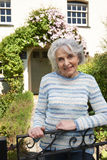 Senior Woman Standing Outside Pretty Cottage Stock Photo