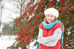 Senior Woman Standing Outside In Snowy Landscape. Smiling Senior Woman Standing Outside In Snowy Landscape Royalty Free Stock Photography