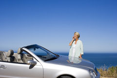 Senior woman standing beside parked convertible car on clifftop overlooking Atlantic Ocean, using mobile phone, smiling, side view Stock Images