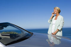 Senior woman standing beside parked convertible car on clifftop overlooking Atlantic Ocean, using mobile phone, smiling, side view Royalty Free Stock Photography
