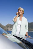 Senior woman standing beside parked convertible car on clifftop overlooking bay, using mobile phone, smiling Stock Images