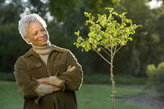 Senior woman standing beside small tree in autumn garden, arms folded, smiling, portrait Royalty Free Stock Images