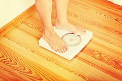 Senior woman standing on weight scale in living room royalty free stock photos