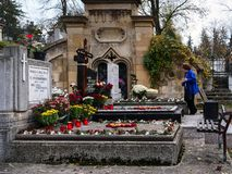 Senior woman stands at a grave paying respect to deceased relatives royalty free stock image