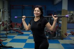 Senior woman stands in the gym with a body bar on her shoulders. close-up. copy space. stock images