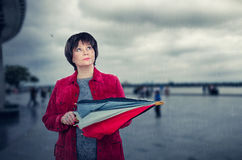 Senior woman stands under sudden rain in Europe Royalty Free Stock Photography