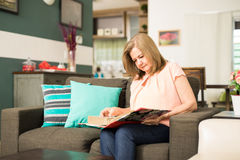 Senior woman staring at a photo album. Beautiful Latin aged lady reviewing her good memories from a photo album in the living room Stock Photo
