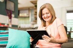 Senior woman staring at photo frame. Joyful senior adult woman enjoying her retirement time looking pictures at the assistance home royalty free stock photo