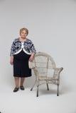 Senior Woman staying near chair Stock Image