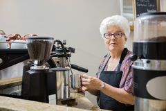 Senior Woman Steaming Milk with Espresso Machine Stock Photos