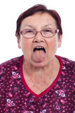Senior woman sticking out tongue Royalty Free Stock Photography