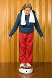 Senior woman stood on scales. Senior women stood on scales Stock Photography