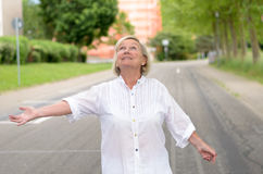 Senior Woman at the Street Checking for Rain Royalty Free Stock Images