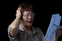 Senior woman in stress from financial bills on black background Royalty Free Stock Images