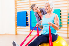 Senior woman with stretch band at fitness. Senior women with stretch band in fitness gym being coached by personal trainer Stock Photo