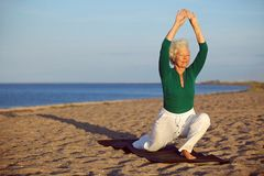 Senior woman stretching on the beach Stock Photos