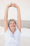 Senior woman stretching on bed Royalty Free Stock Images
