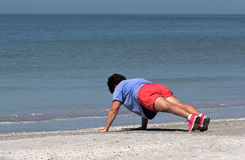 Senior woman stretching and exercising on beach. Stock Images