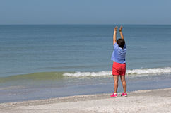 Senior woman stretching and exercising on beach. Royalty Free Stock Image