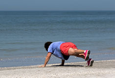 Senior woman stretching and exercising on beach. Stock Photo