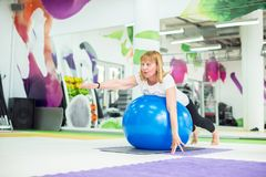 Senior woman is stretching with fitness ball. In gym Royalty Free Stock Photography
