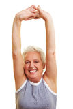 Senior woman stretching her arms. A happy senior woman doing fitness exercises Royalty Free Stock Image