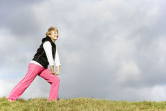 Senior Woman Stretching In Park Stock Photo