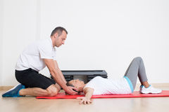 Senior woman stretching with physiotherapist Stock Image