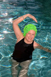 Senior woman stretching pool