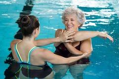 Senior woman stretching in pool. Young trainer helping senior women in aqua aerobics. Senior retired women staying fit by aqua aerobics in swimming pool. Happy stock photography